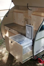 Northern Teardrop Trailer shown with optional electric cooler, running water, sliding cabinet doors